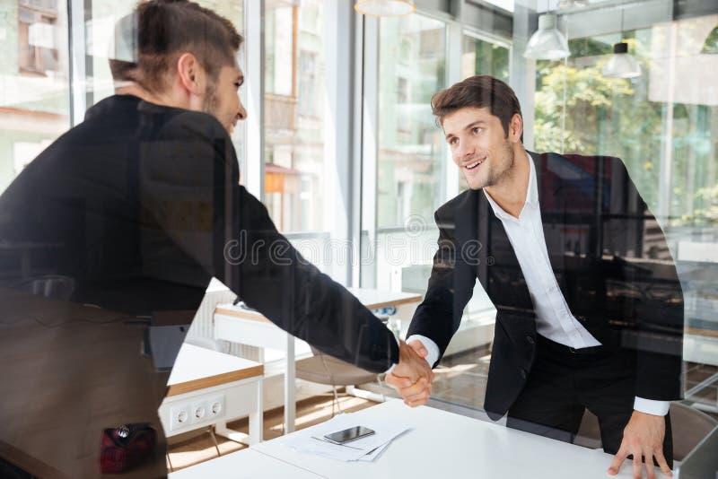 Zwei erfolgreiche Geschäftsmänner, die Hände auf Geschäftstreffen stehen und rütteln lizenzfreie stockbilder