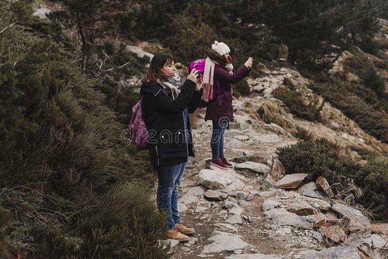 Zwei erfolgreiche Wandererfreundinnen genießen die Ansicht über Bergspitze Glückliche Wanderer in der Natur, die Fotos mit Handy  lizenzfreies stockbild