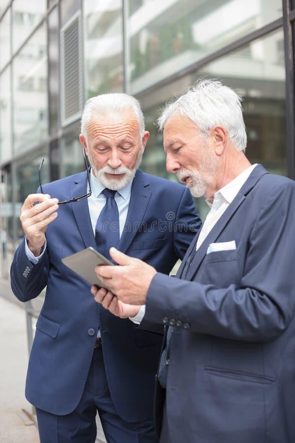 Zwei ernste ältere Geschäftsmänner, die eine Tablettenstellung vor einem Bürogebäude betrachten stockbild