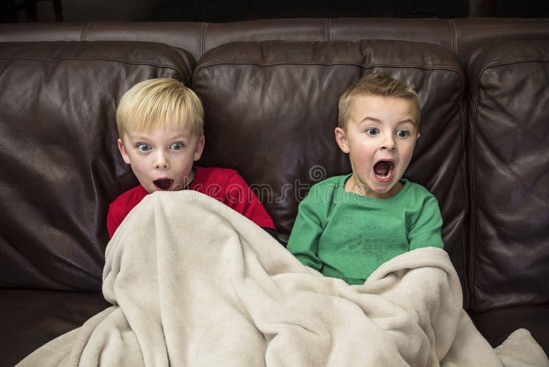 Zwei erschraken die kleinen Jungen, die auf einer Couch sitzen, die fernsieht lizenzfreies stockbild