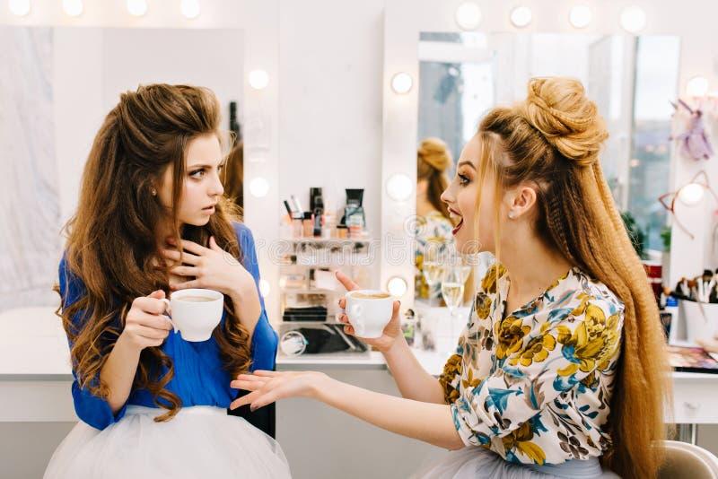 Zwei erstaunten die attraktiven Frauen, die im Sch?nheitssalon sprechen Trinkender Kaffee, Klatsch, bereitend zur Partei vor und  lizenzfreie stockbilder