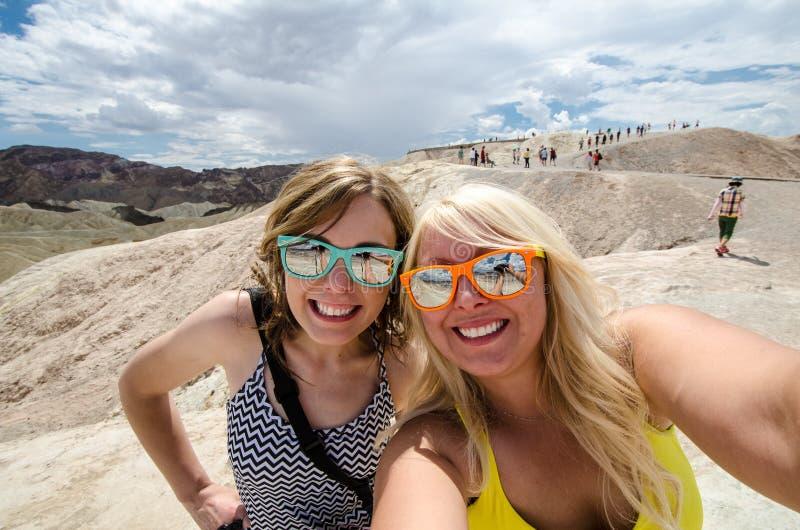 Zwei erwachsene Frauen nehmen ein selfie während am Zabriskie-Punktausblick in Nationalpark Kaliforniens Death Valley lizenzfreies stockbild