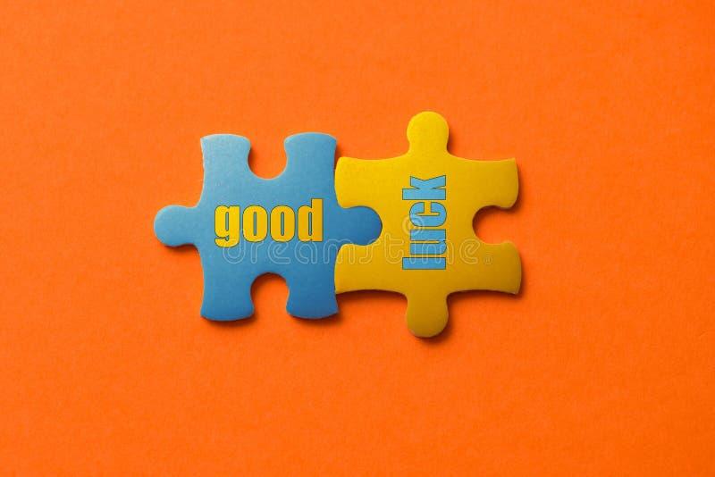 Zwei färbten Details des Puzzlespiels mit gutem Glück des Textes auf orange Hintergrund-, Gelbem und Blauem, nahemhohem lizenzfreies stockfoto