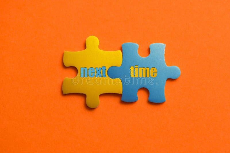 Zwei färbten Details des Puzzlespiels mit Text folgendes Mal auf orange Hintergrund-, Gelbem und Blauem, nahemhohem stockfotografie