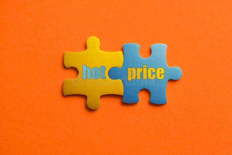 Zwei färbten Details des Puzzlespiels mit Text HEISSEM PREIS auf orange Hintergrund-, Gelbem und Blauem, nahemhohem lizenzfreies stockfoto