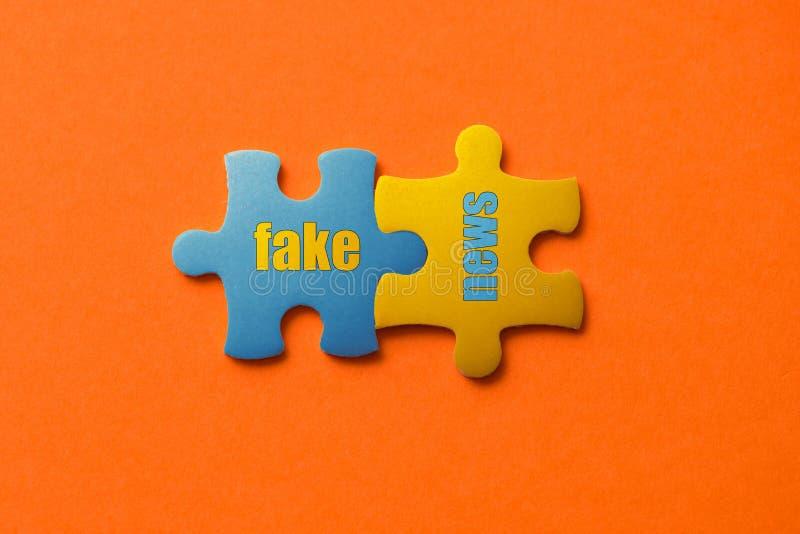 Zwei färbten Details des Puzzlespiels mit Textfälschungsnachrichten auf orange Hintergrund-, Gelbem und Blauem, nahemhohem stockfotografie