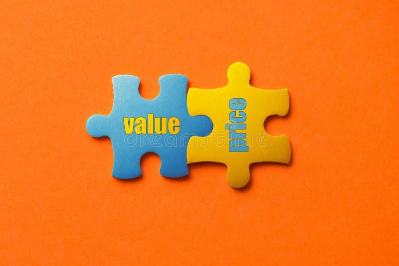 Zwei färbten Details des Puzzlespiels mit Textwertpreis auf orange Hintergrund-, Gelbem und Blauem, nahemhohem stockbild