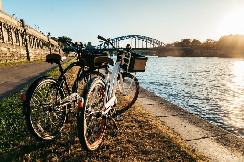 Zwei Fahrräder am Damm auf Sonnenuntergang lizenzfreie stockbilder