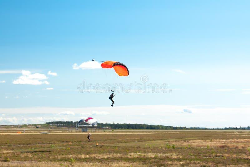 Zwei Fallschirmspringer landen auf bunten Fallschirmen zum Flughafen stockfotografie