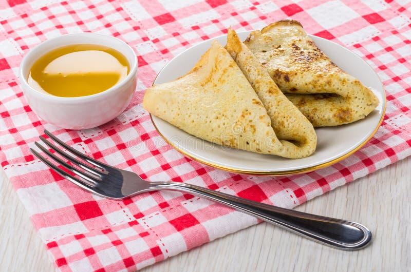 Zwei falteten Pfannkuchen in der Platte, Honig, Gabel auf karierter Serviette stockbilder