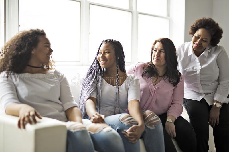 Zwei Familie Freunde, die auf Sofa Together sitzen stockbild
