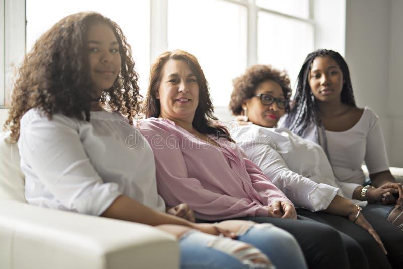 Zwei Familie Freunde, die auf Sofa Together sitzen lizenzfreie stockfotos