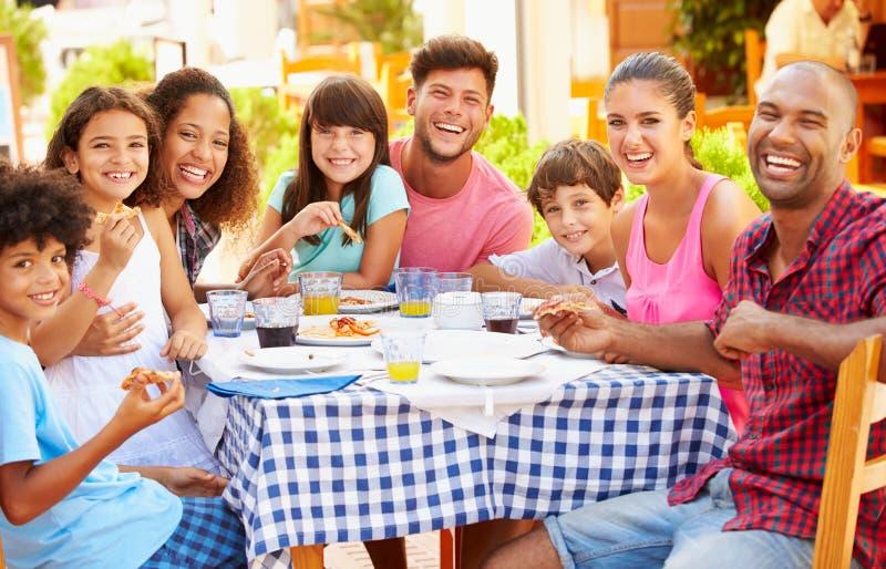 Zwei Familien, die zusammen Mahlzeit Restaurant am im Freien essen stockfotografie