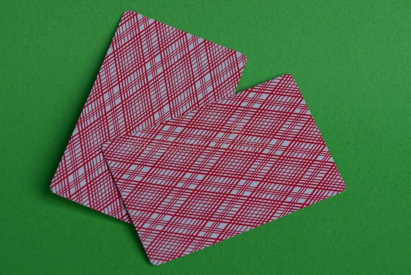 Zwei farbige Spielkarten auf einer grünen Tabelle lizenzfreie stockfotos