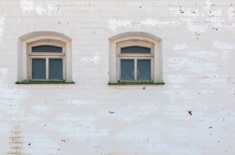 Zwei Fenster in der mediewal Wand des starken Ziegelsteines unter abgenutzter Schicht weißem Gips stockbilder