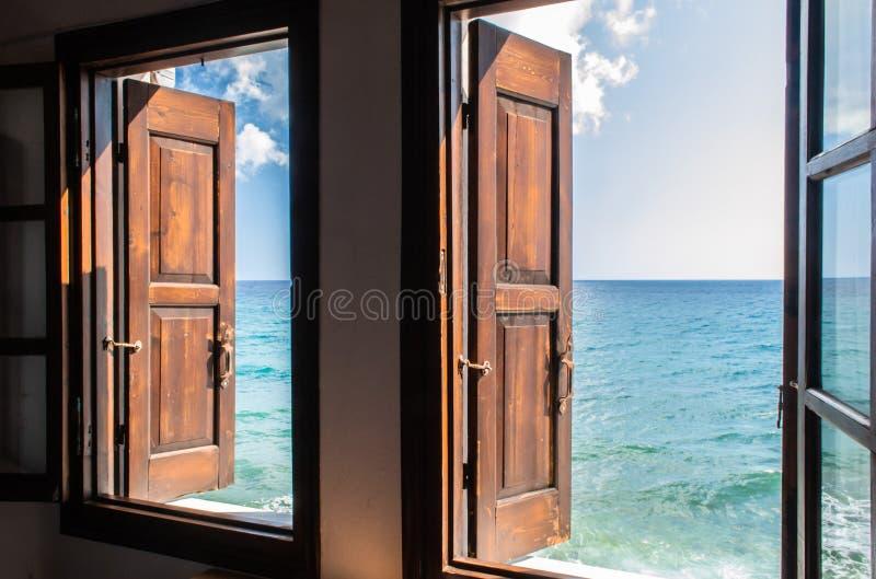 Zwei Fenster mit hölzernen braunen Fensterläden öffnet überraschende Ansicht über aquamarines endloses Meer und blauen Himmel, ke lizenzfreie stockfotografie