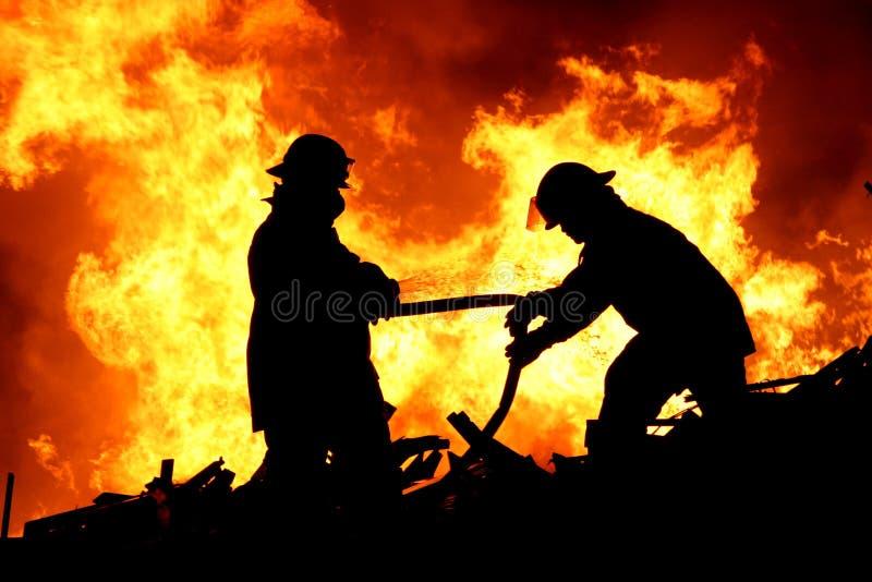 Zwei Feuerkämpfer und -flammen lizenzfreie stockfotos