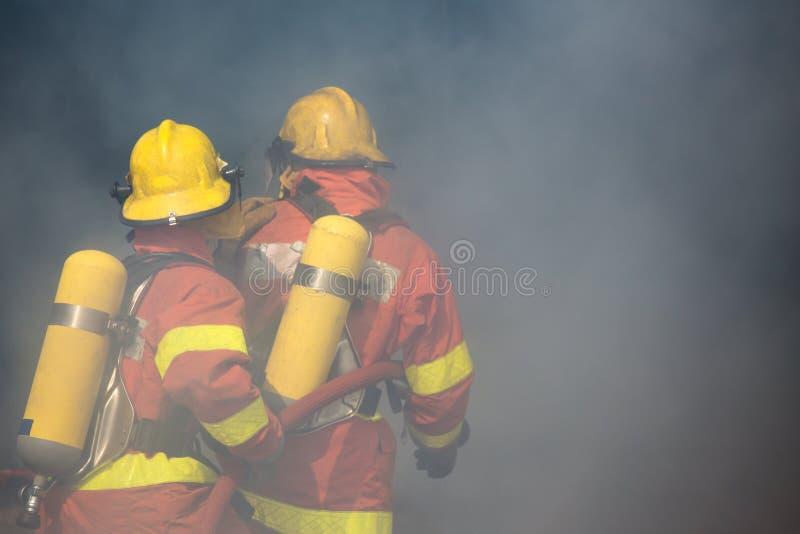 Zwei Feuerwehrmänner bearbeitet Einfassung mit Rauche und Staub stockfoto