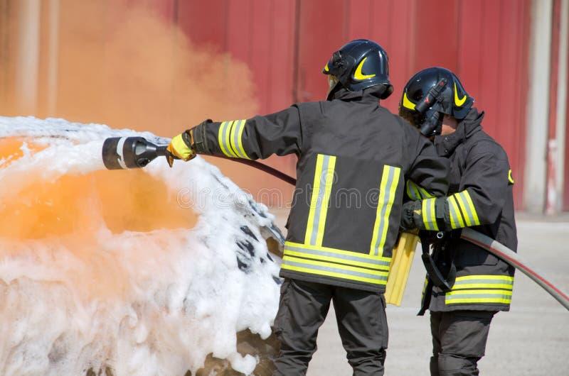 Zwei Feuerwehrmänner in der Aktion mit Schaum lizenzfreies stockbild