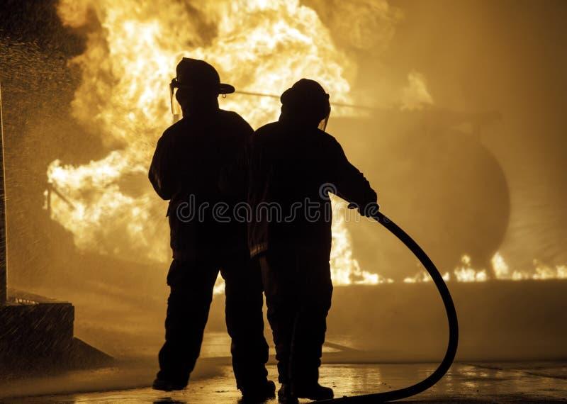 Zwei Feuerwehrmänner, die vor einem Feuer mit Schlauch stehen stockbild