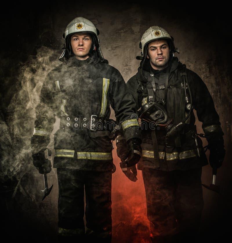 Zwei Feuerwehrmänner in einem Rauche lizenzfreie stockfotos