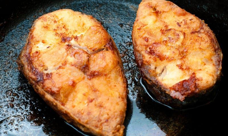 Zwei Fische Steaks, die in der Büffelbutter auf Edelstahl-Bratpfanne gebraten werden stockfotografie