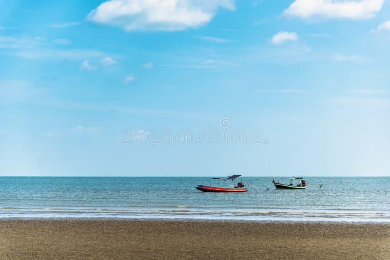 Zwei Fischerboote schwimmen auf das Meer mit einem blauer Himmel- und Wolkenhintergrund stockfotos