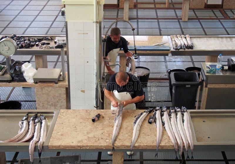 zwei Fischh?ndler, die schwarze Scheidefische im Markt in Funchal Madeira vorbereiten stockfotografie