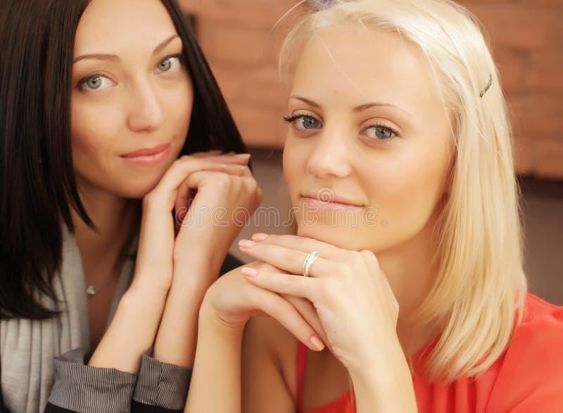Zwei flüsternde und lächelnde Frauen stockbild