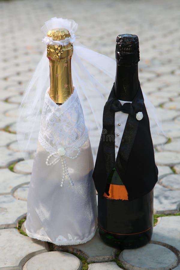 Zwei Flaschen kleideten wie Hochzeitspaare an stockfotos