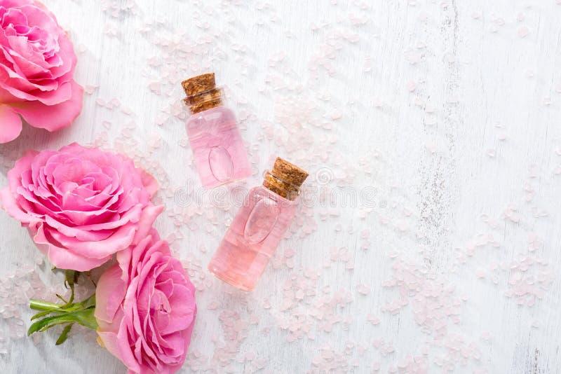 Zwei Flaschen mit rosafarbenem Öl, Kristalle des Mineralbadesalzes und rosa Rosen auf dem Holztisch stockfoto