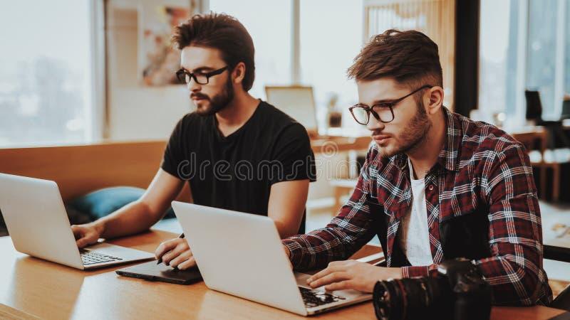 Zwei Fotografen Fosuced auf Arbeit unter Verwendung des Laptops lizenzfreies stockfoto