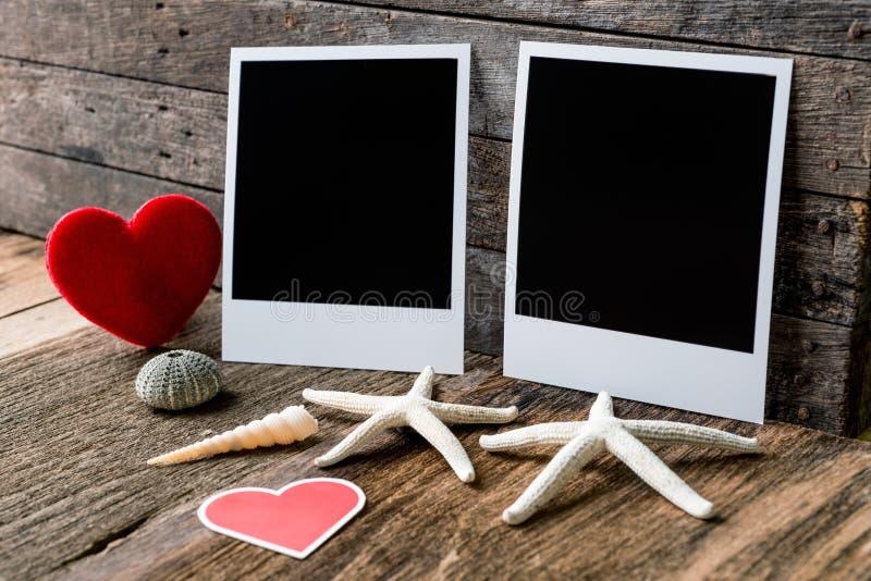 Zwei Fotorahmen und Valentinsgrußtagesherz über hölzernem backgroun lizenzfreie stockfotografie