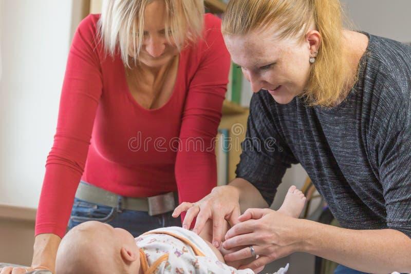 Zwei Frauen ändern Windel zu wenigem Baby lizenzfreie stockfotos
