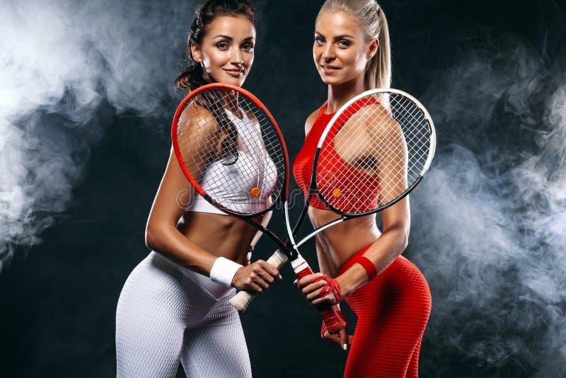 Zwei Frauen Athlet und Tennisspieler auf schwarzem Hintergrund Sport- und Tenniskonzept lizenzfreies stockfoto