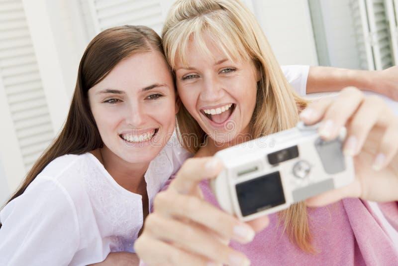 Zwei Frauen auf Patio unter Verwendung der Digitalkamera stockfotografie