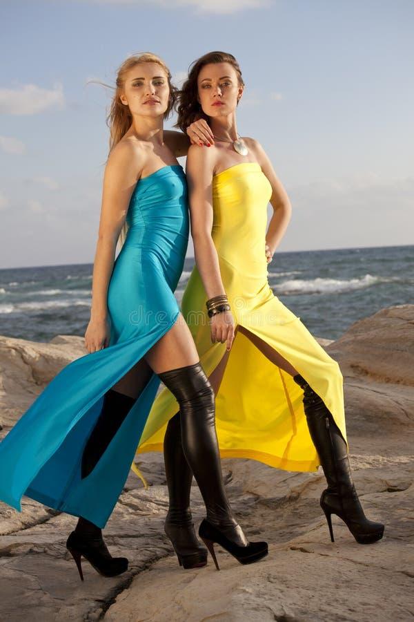Zwei Frauen in den langen Kleidern auf dem Strand stockbild
