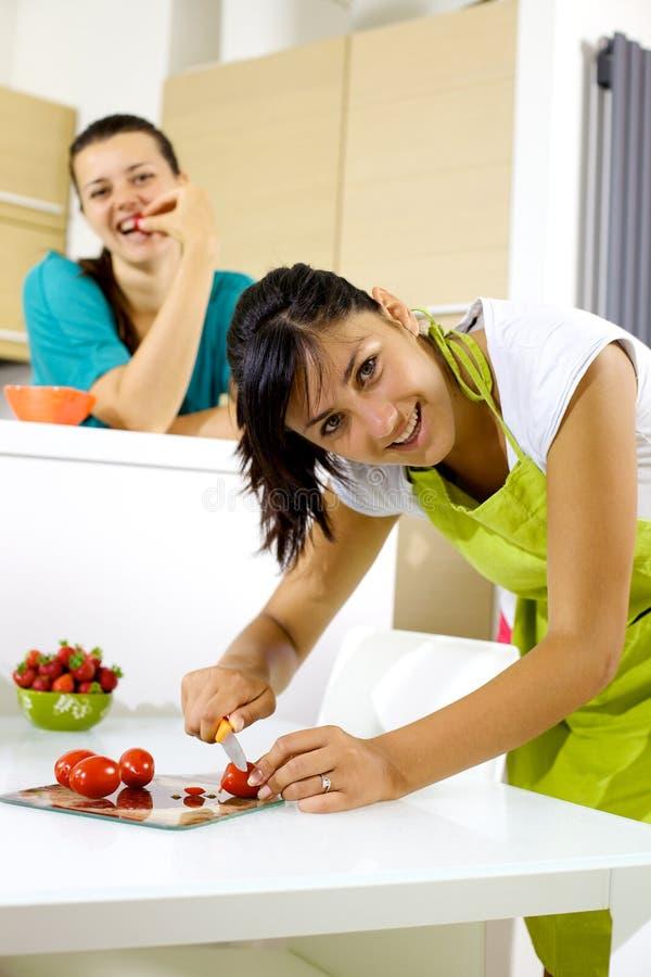 Zwei Frauen in der Küche kochend und essend glücklich stockfotografie