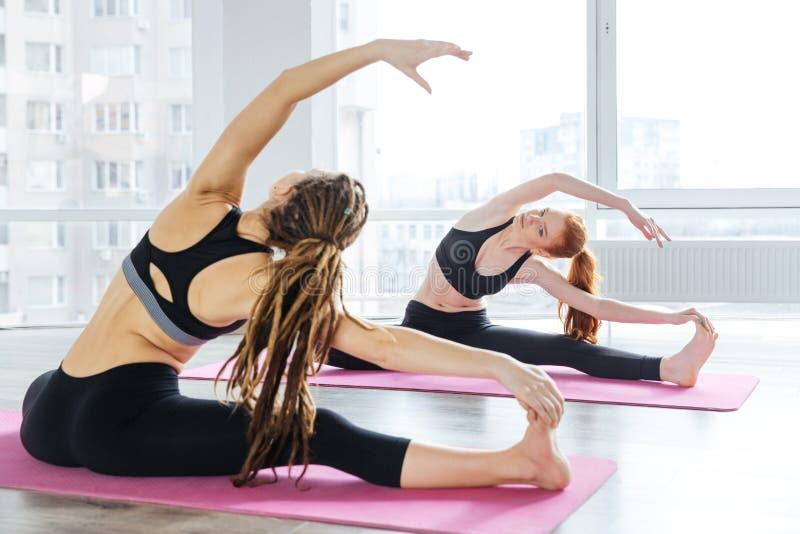 Zwei Frauen, die Übungen in der Yogamitte ausdehnend tun lizenzfreies stockbild
