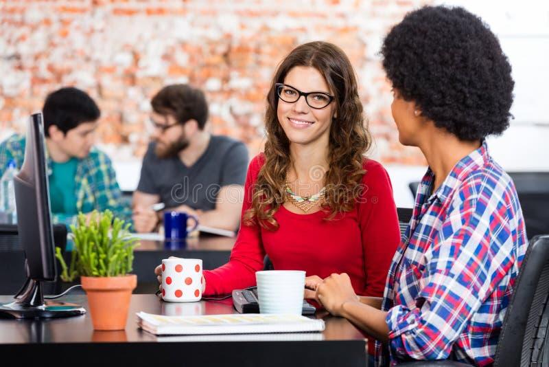 Zwei Frauen, die Arbeitsschreibtischcomputer, Geschäft sitzen lizenzfreies stockfoto