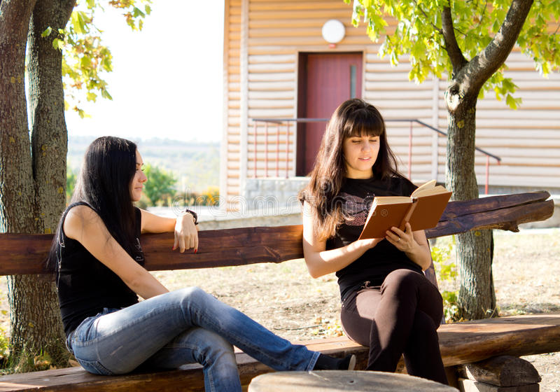 Zwei Frauen, die auf Bank stationieren lizenzfreies stockbild