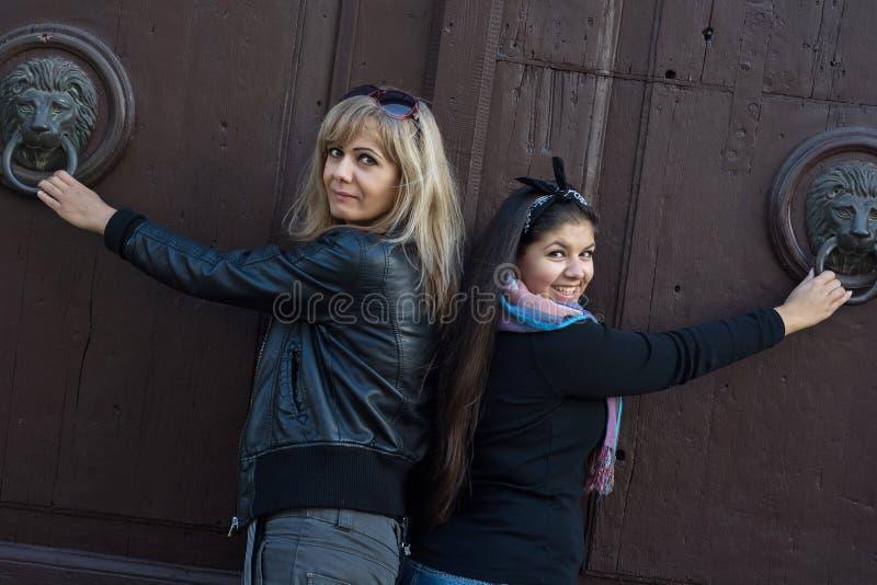 Zwei Frauen, die auf der Tür mit Klopfern klopfen lizenzfreies stockfoto