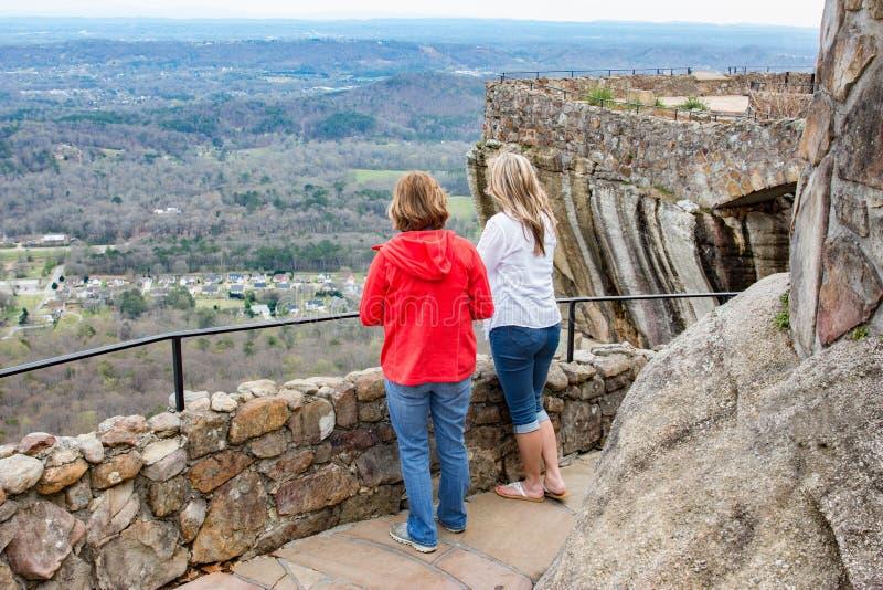 Zwei Frauen, die auf einer Klippe schaut unten auf Landschaft hoch stehen stockfotos