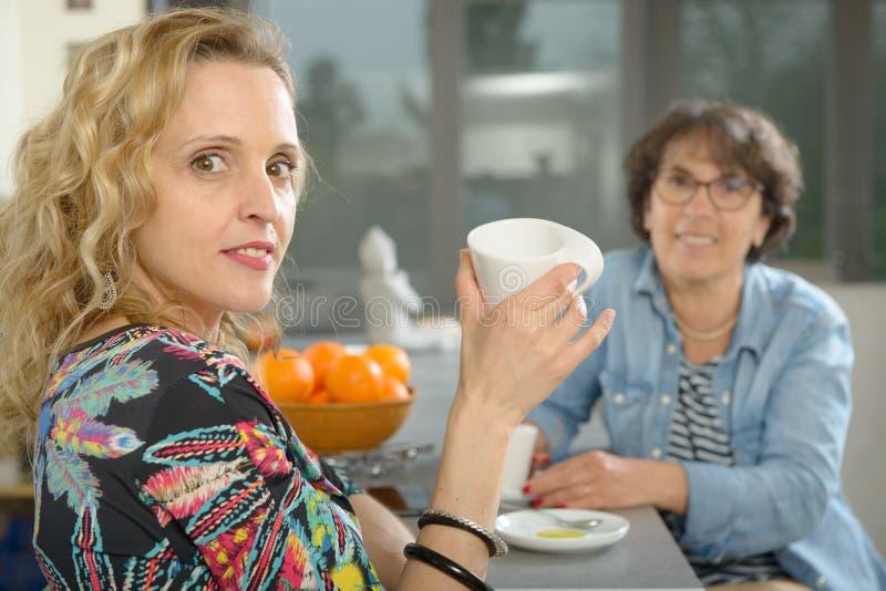 Zwei Frauen, die bei Tisch in der Küche und in trinkendem Kaffee sitzen stockfotos