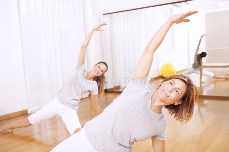 Zwei Frauen, die eine Eignung machen, exercisen im Synchrony lizenzfreie stockfotografie