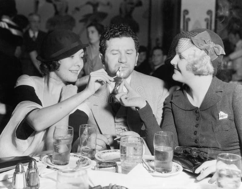 Zwei Frauen, die eine Zigarette für einen Mann beleuchten (alle dargestellten Personen sind nicht längeres lebendes und kein Zust stockfotografie
