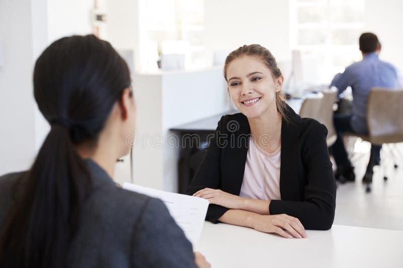 Zwei Frauen, die an einem Interview in einem Bürogroßraum sitzen lizenzfreie stockfotos