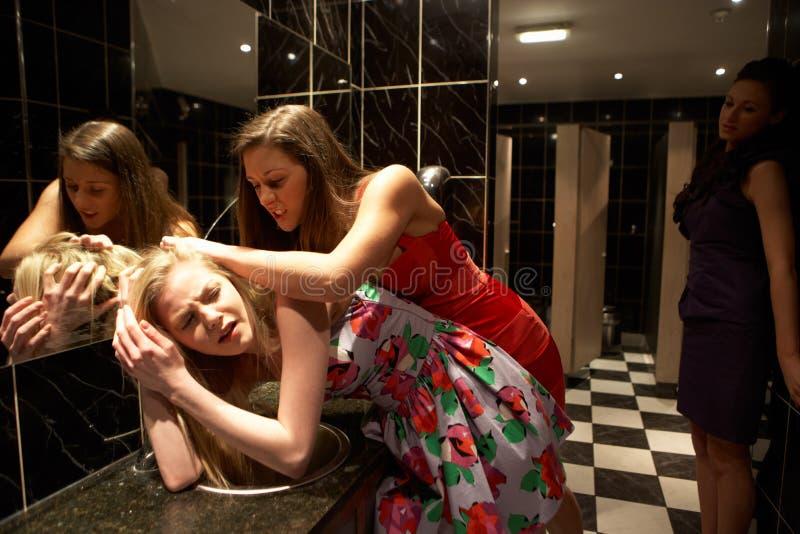 Zwei Frauen, die einen Kampf im Badezimmer haben lizenzfreie stockbilder
