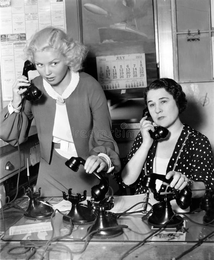 Zwei Frauen, die an einer Telefonbank arbeiten (alle dargestellten Personen sind nicht längeres lebendes und kein Zustand existie lizenzfreie stockbilder