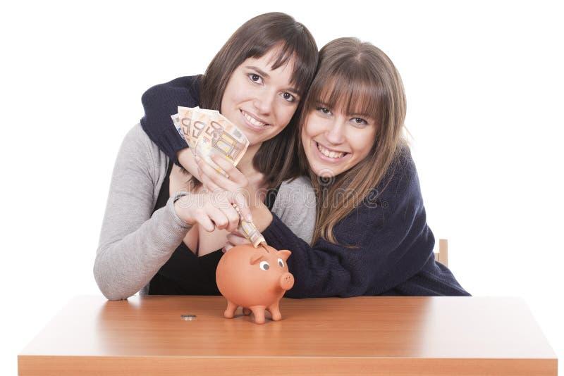Zwei Frauen, die Geld anhalten stockfotografie